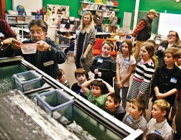 HOLLY PELCZYNSKI - BENNINGTON BANNER Third graders at the Village School of North Bennington watch in anticipation as Trout eggs get placed in the fish tank in their classroom. The students are learning about the lifecycle of Trout from fishing expert Barry Mayer, volunteer and educated with the Southern Vermont chapter of Trout unlimited, after the eggs are placed they will stay in the classroom, grow, and then be released back into the wild.